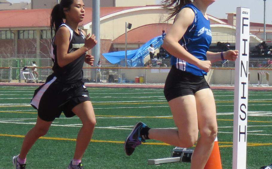 Seoul American's Mariah Meredith and Humphreys' Nicole Castro compete in the girls 1,600 during Saturday's Korea track and field meet. Meredith won in 5 minutes, 51.7 seconds.