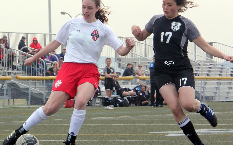 Nile C. Kinnick's Katrina Reid and Zama's Kimi Stuckey pursue the ball during Saturday's Kanto Plain/DODDS Japan girls soccer match. The Red Devils won 3-0, with Reid - a former Trojan playing her first match against her old team - scoring a goal and adding an assist.