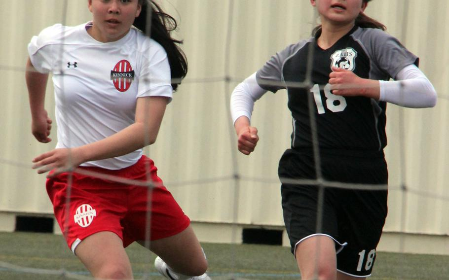 Nile C. Kinnick's Kiralyn Kawachi buries the ball into the net while Zama's Leah Parish watches during Saturday's Kanto Plain/DODDS Japan girls soccer match. The Red Devils won 3-0, with Reid - a former Trojan playing her first match against her old team - scoring a goal and adding an assist.