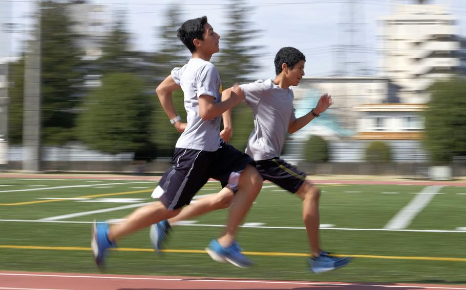 Two runners from the World Records Camp at Yokota Air Base, Japan practice their running form Sunday, March 29, 2015. Four former Olympians visited Yokota as part of a track clinic for area high school and middle school athletes.