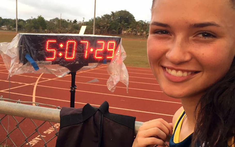 Guam High sophomore Emma Sheedy stands beside the clock showing her winning time of 5:07.29, a new island record in the 1,500-meter run. She broke the old mark of 5:11.47 set last season by Alison Bowman of John F. Kennedy High School and beat her own personal best by six seconds. She also won the 800 title in 2:25.86.