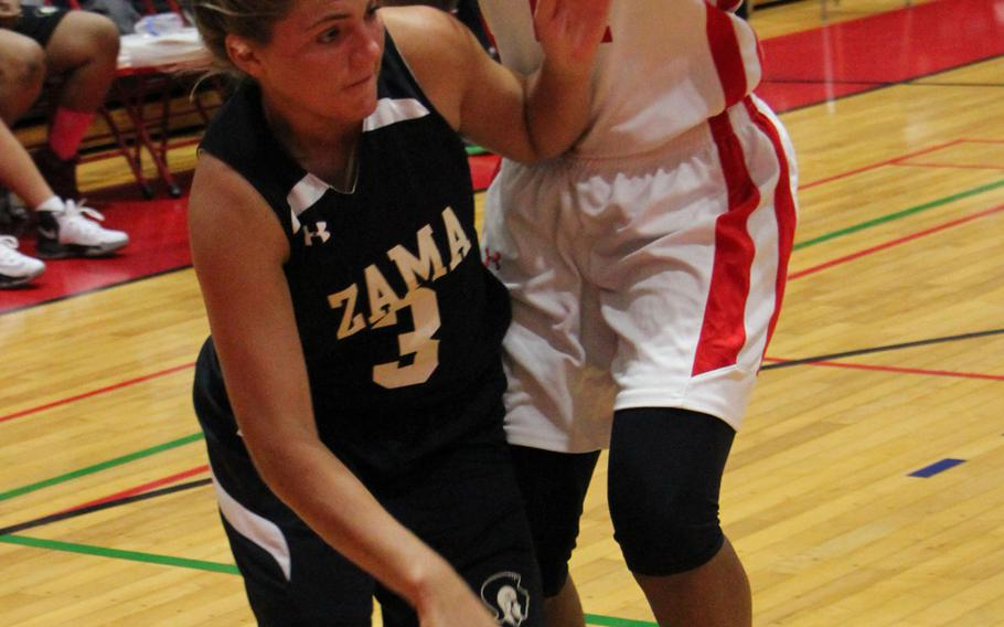 Zama's Ally Chiarenza tries to drive around Nile C. Kinnick's Taylor Cobb during Wednesday's girls basketball game. The Division II Trojans edged the D-I Red Devils 35-31 in overtime.