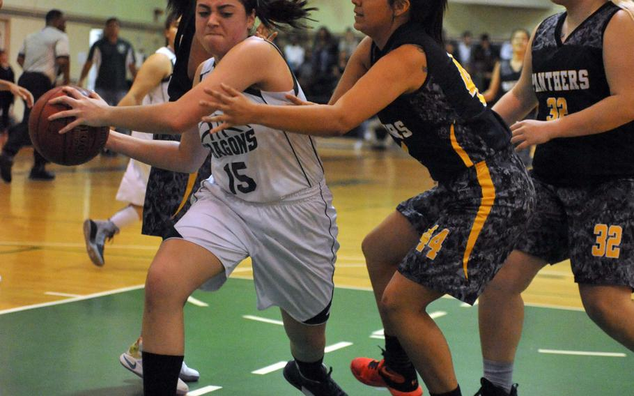 Kubasaki's Reaven East tries to keep the ball away from Kadena's Gracie Graham and Lauren Erp in Friday's girls basketball game, won by the Panthers 31-25 for their13th straight district championship.