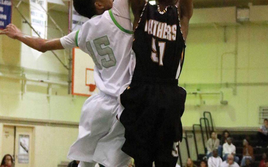Kadena's Alec Peel and Kubasaki's Ilijah Washington sky for a rebound in Friday's boys basketball game, won by the Panthers 67-44 to clinch their second district championship in three seasons.