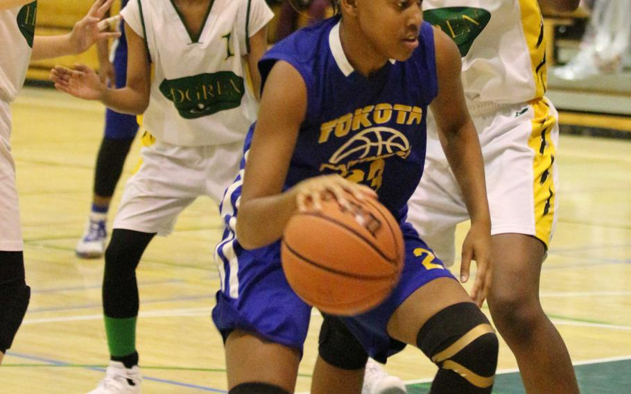 Yokota's Britney Bailey looks for room to operate against Robert D. Edgren's Ja'la Wade during Friday's girls basketball game, won by the Eagles 55-43.