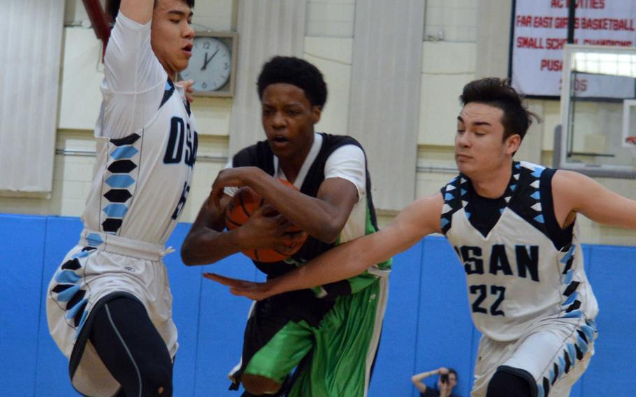 Daegu's Kevin Williams tries to work his way between Osan's Sung DeAngelo and Matthew Burbee during Saturday's boys basketball game, won by the Cougars 61-30.