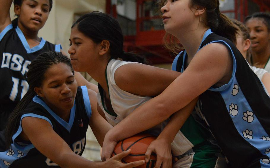 Daegu's Ki'inani Royer has the ball tied up by Osan's Monique Wilson and Elizabeth White as Cougars teammate Krystal Williams moves in to help during Saturday's girls basketball game, won by the Cougars 39-6.
