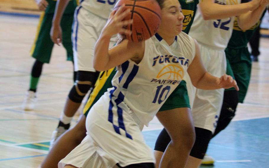 Yokota's Taylor Peche tries to keep a handle on the ball against Robert D. Edgren's Christina Taylor during Saturday's girls basketball game, won by the Panthers 50-40.