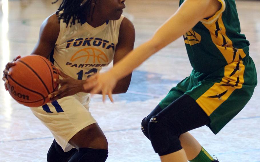 Yokota's Jamia Bailey looks for operating room against Robert D. Edgren's Karen Anastos during Saturday's girls basketball game, won by the Panthers 50-40.