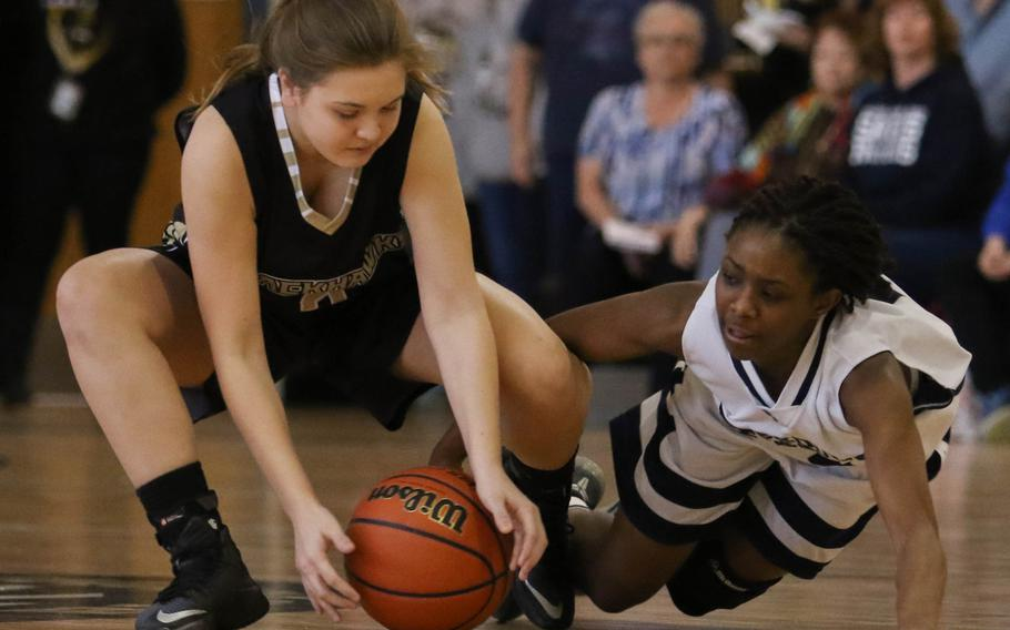 Humphreys' Hayden Orr and Seoul American's Alysa Neal scrum for the ball during Saturday's girls basketball game. The Blackhawks got their first win in the school's four-year history over the Falcons, 40-37.