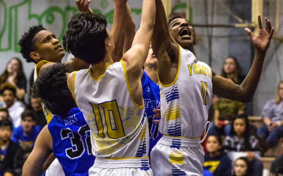 Yokota's Kishaun Kimble-Brooks skies for a rebound amid a sea of teammates and St. Mary's defenders during Tuesday's boys basketball game, won by the Panthers 63-45.