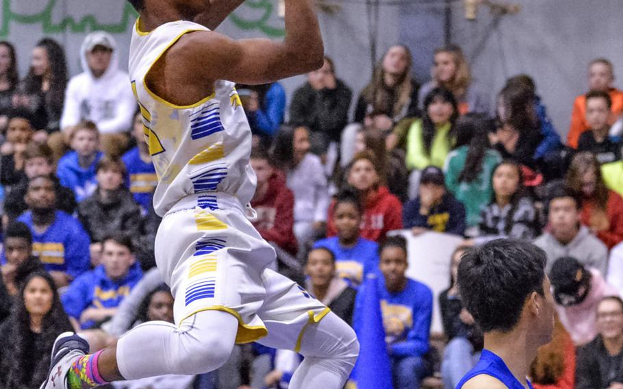 Yokota's Marquis Smith-Brown skies for a shot over St. Mary's Jongdae Kim during Tuesday's boys basketball game, won by the Panthers 63-45.