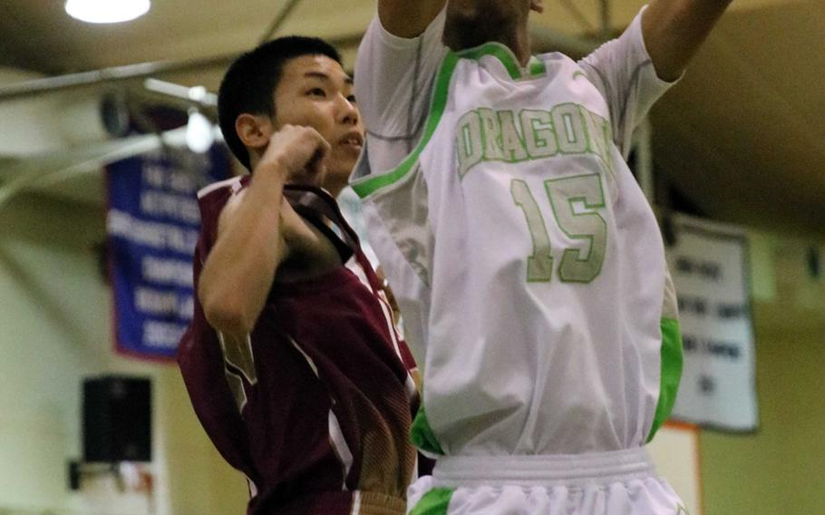 Kubasaki's Ilijah Washington skies for a rebound against a Naha Kokusai defender during Wednesday's boys basketball game, won by the Dragons 72-69 in overtime.