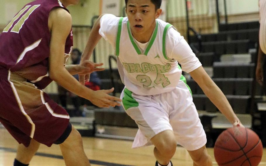 Kubasaki's Jhean Natividad dribbles against a Naha Kokusai defender during Wednesday's boys basketball game, won by the Dragons 72-69 in overtime.