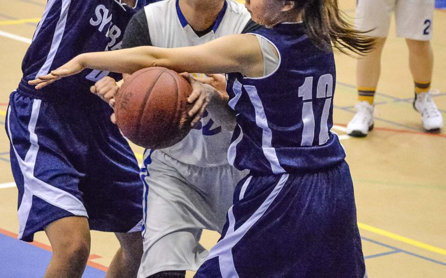 Yokota's Irene Diaz tries to drive between Sacred Heart's Alisa Belitz and Lisa Sato during Thursday's girls basketball game, won by the Panthers 59-19.