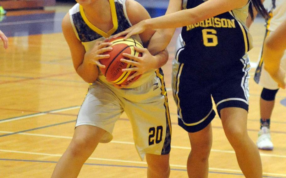Kadena's Yasmine Doss and Morrison Academy of Taiwan' Juri Yanamoto tie up for the ball during Friday's girls game in the 2nd Taipei American School Basketball Exchange. The defending Far East Division I Tournament champion Panthers won 63-46.