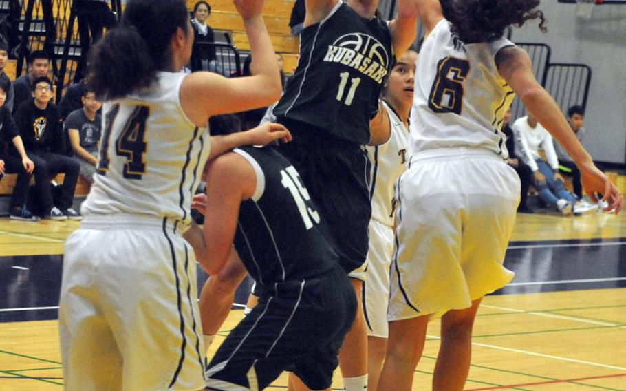 Kubasaki's Chloe' Stevens puts up a shot over teammate Reaven East and between two Taipei American defenders during Friday's girls game in the second Taipei American School Basketball Exchange. The host Tigers beat the Dragons 71-29.