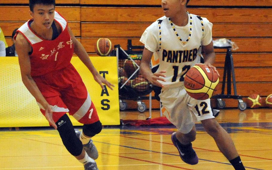Kadena's Anthony Laney dribbles against a Yilan defender during Saturday's boys game in the 2nd Taipei American School Basketball Exchange. The Panthers lost for the first time in six games they've played in Taipei, 80-77 to Yilan, a local Chinese team.