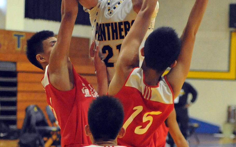 Kadena's Justin Wilson skies over three Yilan Senior High School defenders during Saturday's boys game in the 2nd Taipei American School Basketball Exchange. The Panthers lost for the first time in six games they've played in Taipei, 80-77 to Yilan, a local Chinese team.