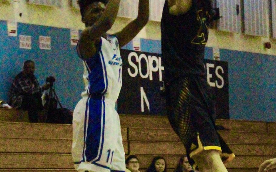 Seoul American's Josh Nix shoots over Taejon Christian Jin Hyun Jung during Saturday's Korea boys basketball game, won by the Falcons 74-27.