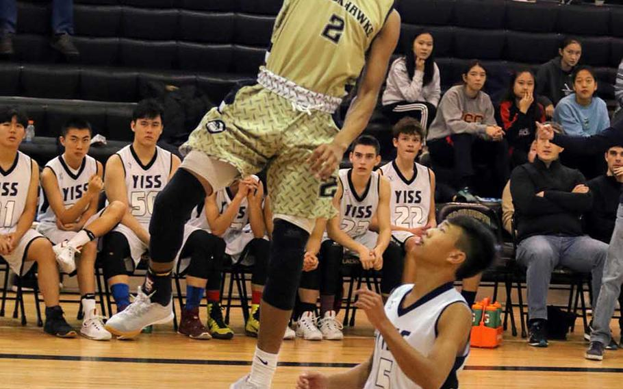 Humphreys' Tyrell Alexander skies for a shot over Yongsan's Max Choi during Saturday's 76-37 win by the Guardians over the host Blackhawks in Korea Blue boys basketball.