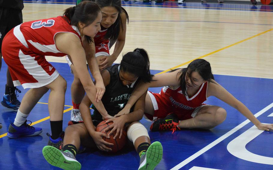 Daegu's Kamala Kenny finds herself and the ball tied up by Yongsan's Gayoon Choi, Rebecca Kim and Amelia Tang during Saturday's girls basketball game, won by the Guardians 38-4.