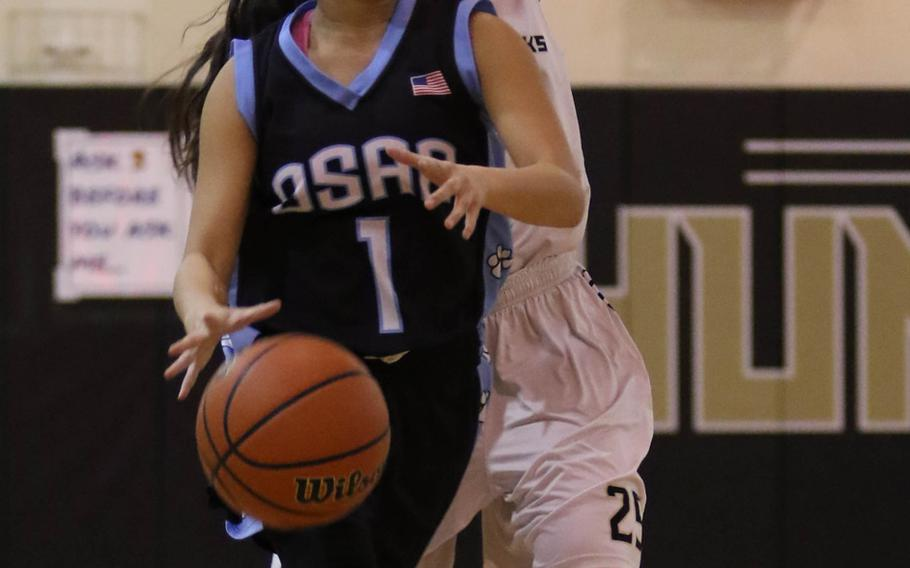 Osan's Jana Rafi dribbles ahead of Humphreys' Cleo Cody during Wednesday's girls basketball game. The visiting Cougars won 51-25.