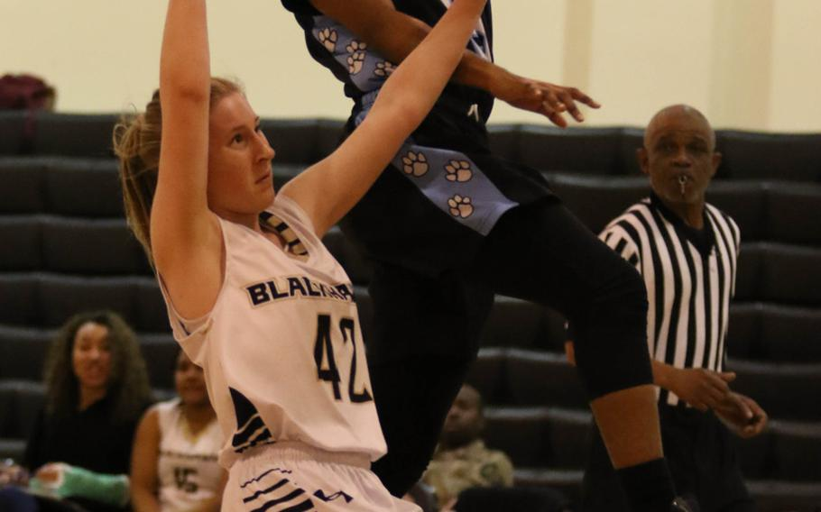 Osan's Danielle Dawson skies over Humphreys' Kaelin Elliott for a shot during Wednesday's girls basketball game. The visiting Cougars won 51-25.