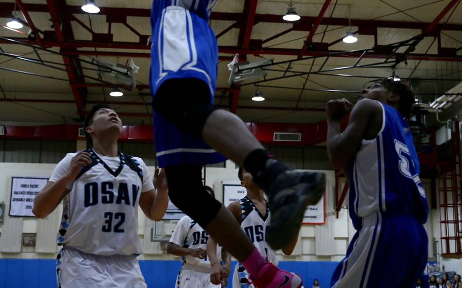 Seoul American's DeAndre Metcalf slam dunks over teammate Levi Johnson and Osan's Justin Maglalang during Monday's boys basketball game. The visiting Falcons won 74-41.