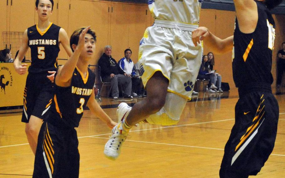 Yokota's Kishaun Kimble-Brooks puts up a shot between American School In Japan defenders on Day 1 Thursday of the first ASIJ Kanto Classic. The two-time defending Far East Division II champion Panthers edged the Mustangs 66-62.