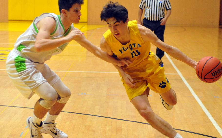 Yokota's Hunter Cort dribbles past Kubasaki's Bobby Riegert in a battle of two-time defending Far East Tournament champions on Day 2 Friday of the 1st ASIJ Kanto Classic. The Division II Panthers and reigning D-II MVP Cort downed the Division I Dragons 50-35 and earned the top seed in Saturday's single-elimination playoffs.