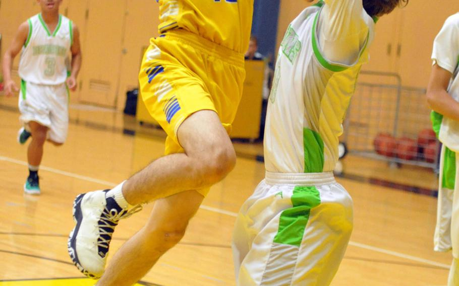 Yokota's Hunter Cort goes up for a shot against Kubasaki's Jonny Hoppe in a battle of two-time defending Far East Tournament champions on Day 2 Friday of the 1st ASIJ Kanto Classic. The Division II Panthers and reigning D-II MVP Cort downed the Division I Dragons 50-35 and earned the top seed in Saturday's single-elimination playoffs.