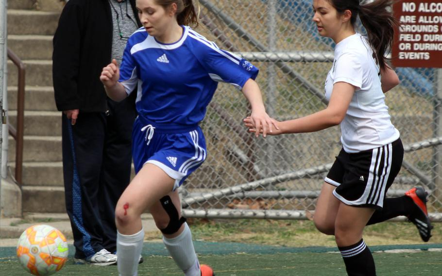 Seoul American's MK Dunleavy dribbles ahead of Daegu's Irene Halferty during Saturday's girls soccer match, won by the Falcons 3-0.