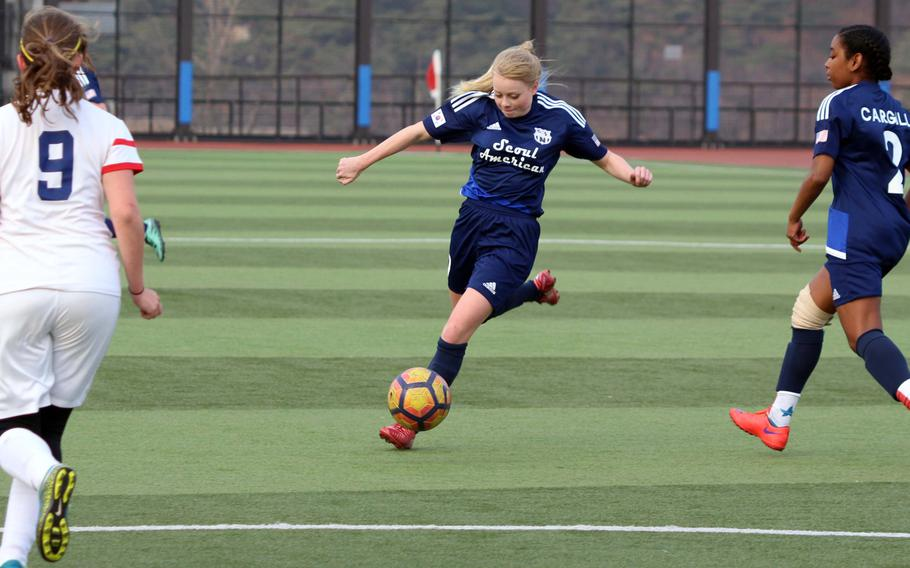 Seoul American's Amy Arnold lets fly between Yongsan's Dora Zoeller and Falcons teammate Natalie Cargill during Wednesday's girls soccer match. The visiting Falcons won 6-2.