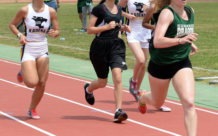 Kubasaki freshman Elizabeth Joy, far right, and Kadena senior Sierra Fitzgerald, far left, pass lapped runners en route to the finish of the 1,600 during Friday's 13th Mike Petty Memorial Track and Field Meet. Joy won in 5 minutes, 46.32 seconds; Fitzgerald was second in 5:47.74.