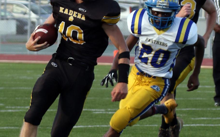 Kadena QB Cody Sego turns the corner past Yokota's Jimmy Dewberry during Saturday's high school football game, won by Kadena 44-0.