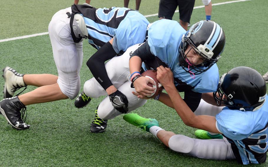 Osan running back Easton Clark tries to bull his way through Cougars defenders Zachary Johnson and Marcus Inthavixay.