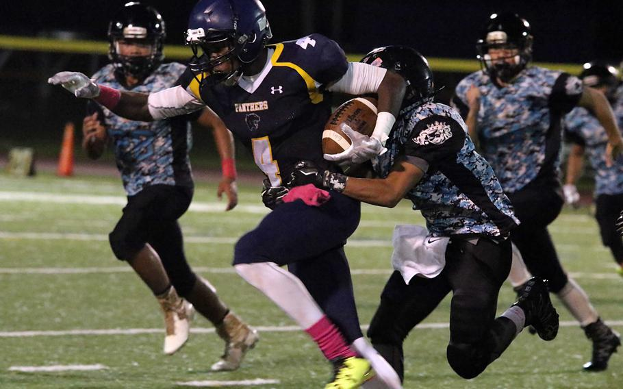 Will Sanders of Guam High drags a Southern defender into the end zone for yardage