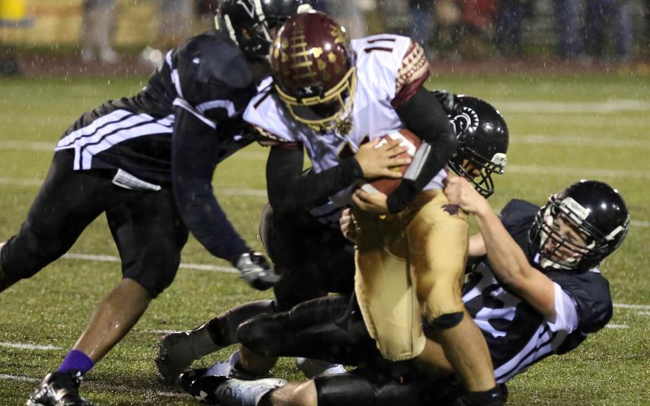 Matthew C. Perry ballcarrier Elijah Lebron tries to burrow his way through a gaggle of Zama defenders.