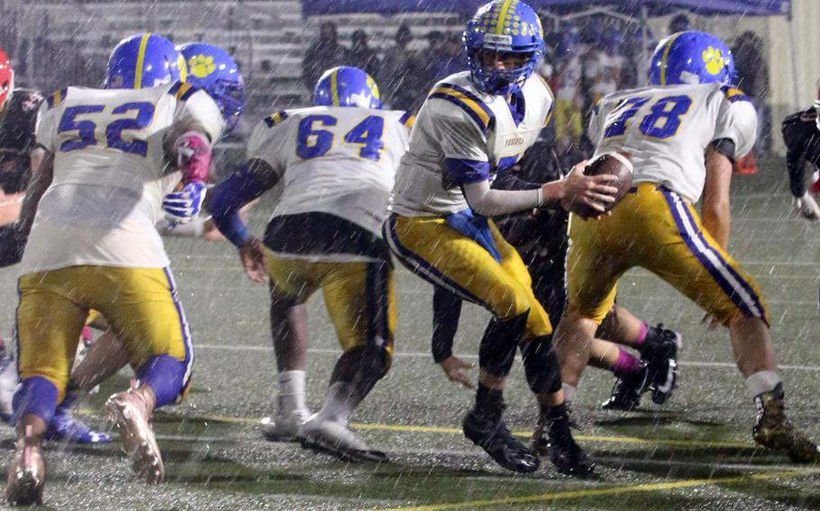 Yokota quarterback Nathan Rundle turns to hand off to Jalen Harrison.