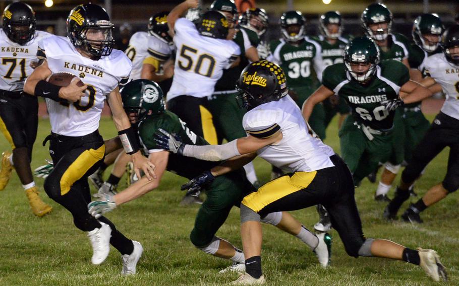 Kadena quarterback Cody Sego looks to elude a Kubasaki tackle.