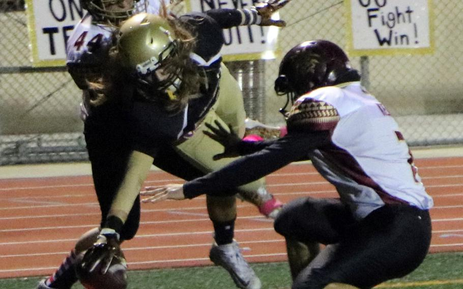 Humphreys receiver Owen Williams stretches for the corner of the end zone between Matthew C. Perry defenders during Friday's football game, won by the Samurai 20-10.