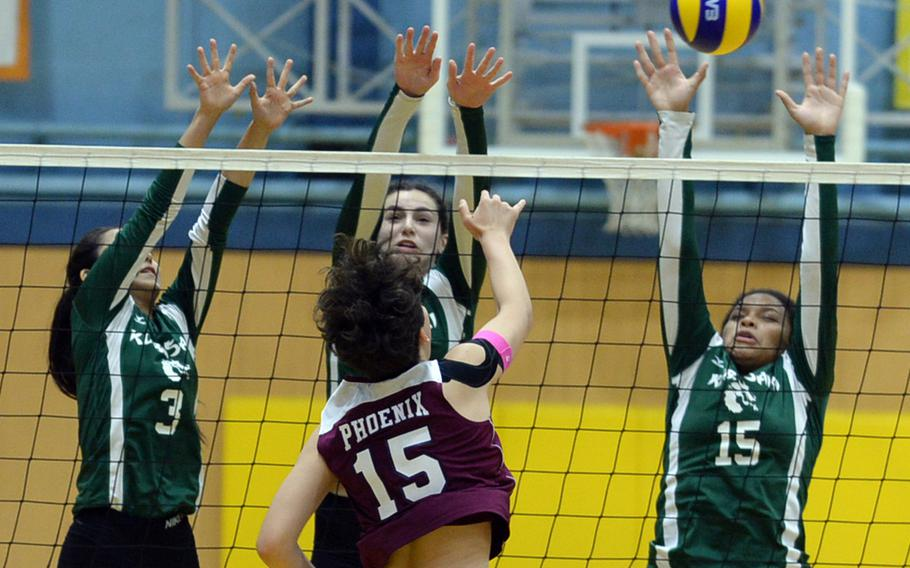 Seisen's Amanda Wood powers a spike through the triple block of Kubasaki's Mimi Larry, Abigail Robinson and Yoselin Johnson during Saturday's American School In Japan-YUJO III girls volleyball tournament. The Phoenix swept the Dragons in straight sets.