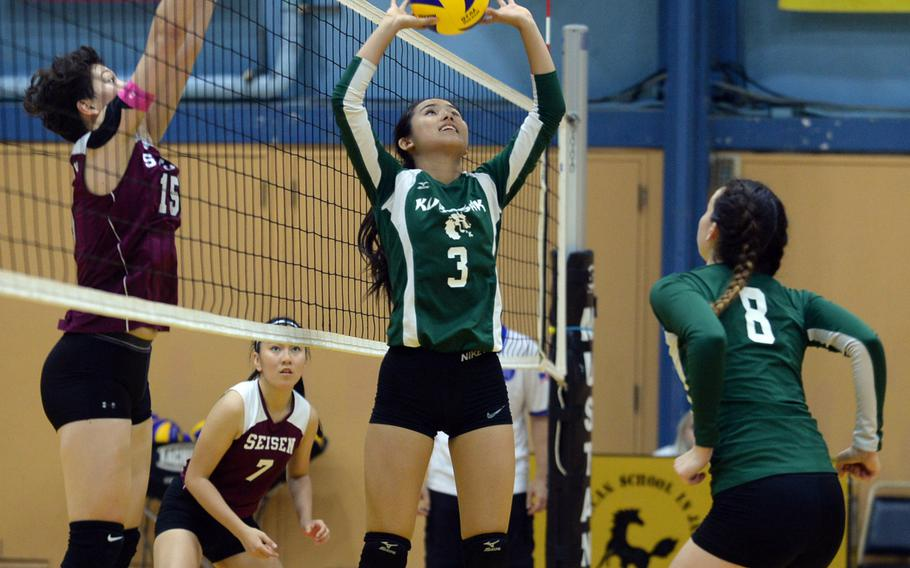 Kubasaki setter Mimi Larry readies a set for teammate Abigail Robinson as Seisen's Amanda Wood jumps to block at the net during Saturday's American School In Japan-YUJO III girls volleyball tournament. The Phoenix swept the Dragons in straight sets.