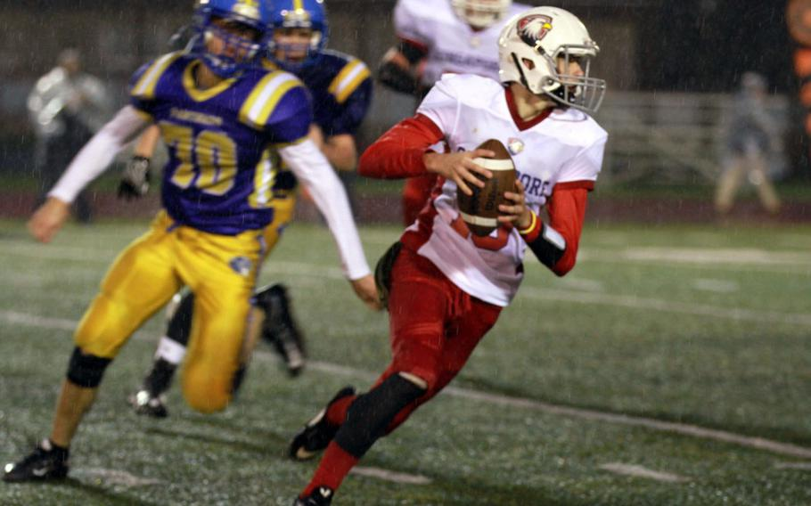 Singapore quarterback Austin Napierski tries to elude the rush of Yokota's Austin Fisher during Monday's football game, won by the Panthers 25-6.