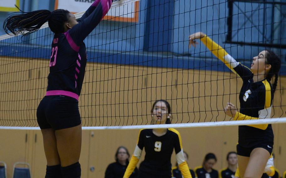 American School In Japan's Ariel Fuchs has a shot blocked by Yokota's Britney Bailey during Wednesday's volleyball match, won by the Mustangs 25-15, 25-19, 28-26.