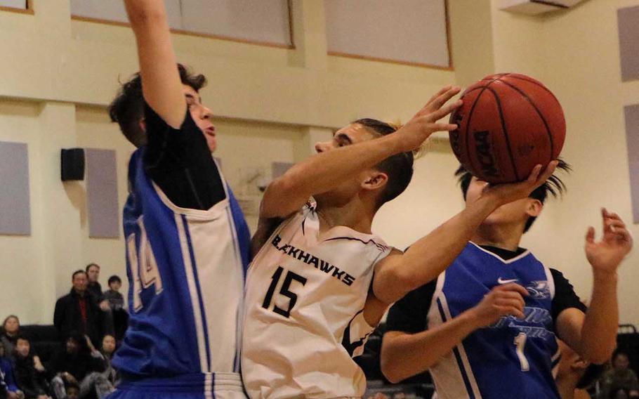 Humphreys' Joshua Weaver tries to shoot between Seoul American's Blake Christianson and Caleb Lee during Wednesday's Korea boys basketball game, won by the Blackhawks 80-34.