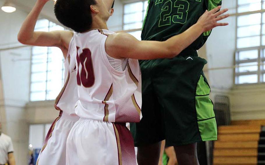Kubasaki's Damian Dorval shoots over two Naha Kokusai defenders during Saturday's boys pool-play game in the 12th Okinawa-American Friendship Basketball Tournanment. The Dragons routed Naha Kokusai 66-40.