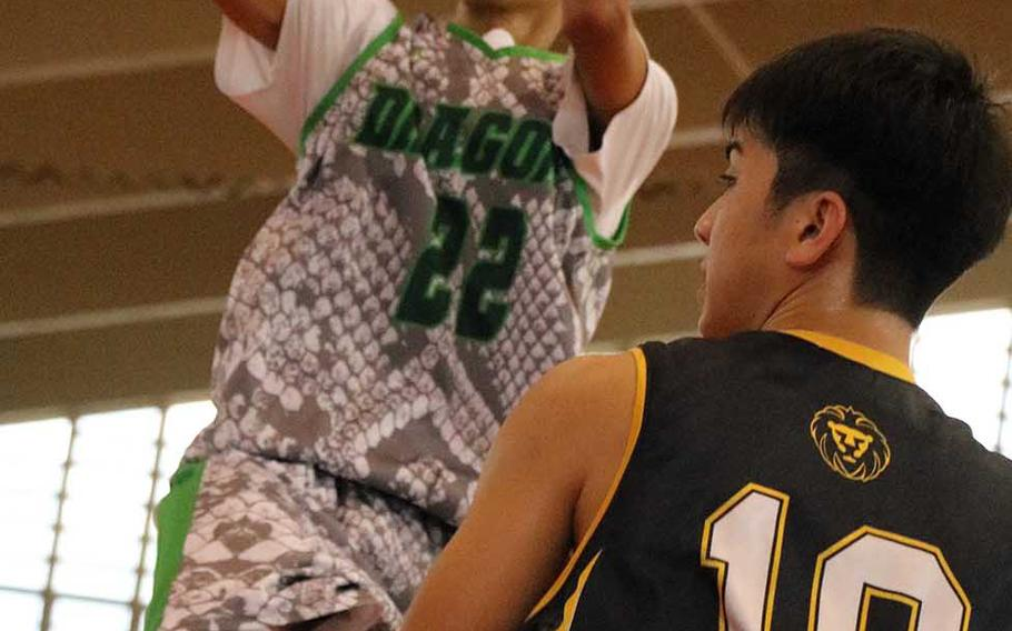 Kubassaki's Elonzo Higginson III jump shoots over a Kitanakagusuku defender during Saturday's boys pool-play game in the 12th Okinawa-American Friendship Basketball Tournament. The Dragons edged the Fighting Lions 58-57 in a rematch of last year's championship game, won by Kitanakagusuku 63-60.