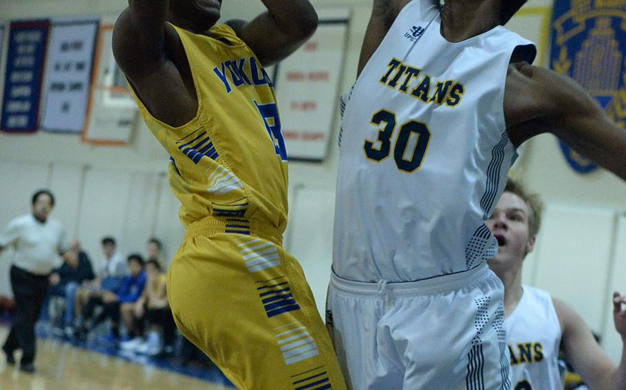 Yokota's Jimmy Dewberry puts up a shot against St. Mary's Satish Karthikeyan during Friday's Japan boys basketball game, won by the Panthers 52-32.